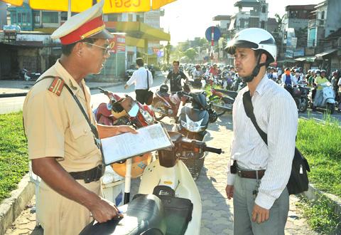 Cảnh sát giao thông Hà Nội xử lý chủ xe mô tô không có giấy chứng nhận bảo hiểm bắt buộc trách nhiệm dân sự. Ảnh: Đức Long.